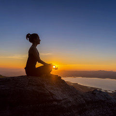 Woman with yoga posture on the mountain at sunset.