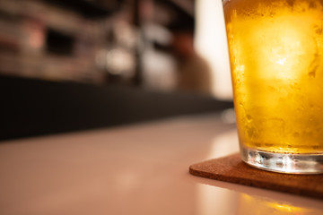 glass of cold craft beer and shadow on white table at bar