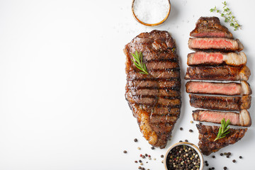 Printed kitchen splashbacks Steakhouse Two grilled marbled beef steaks striploin with spices isolated on white background, top view with copy space