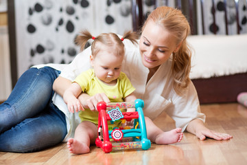 Mother and baby daughter playing together with colorful logical toy on the floor of a bedroom at home