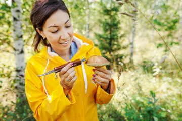 A woman in a bright yellow jacket picking mushrooms in an autumn forest. Concept of outdoor recreation