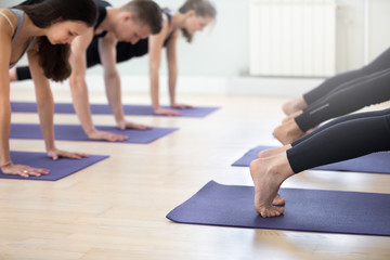 Group of young sporty people practicing yoga lesson, doing Push ups or press ups exercise, phalankasana, Plank pose, working out, indoor, students training in club, studio close up. Well-being concept