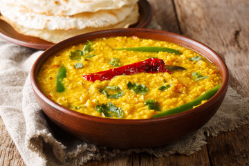 Delicious Dal Tadka recipe of yellow lentils with spices, herbs and chili pepper close-up in a bowl. horizontal