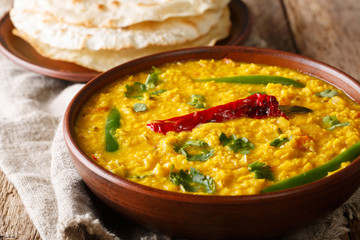 Spicy Indian thick soup Dal Tadka is a popular North Indian recipe close up in a bowl. Horizontal