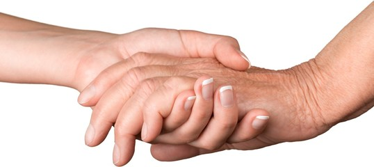Young Woman's Hand Touching and Holding an Old Hand