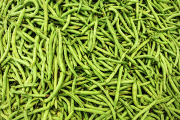 Pile of wet green (string) beans  displayed on food market. Abstract healthy nutrition background.