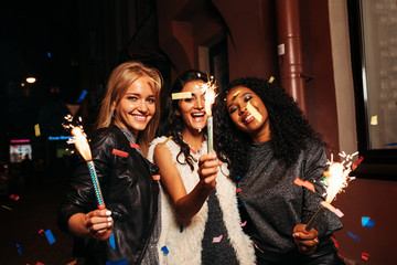 Three female friends holding sparklers on street