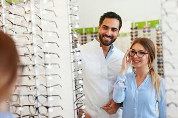 Eye Doctor With Woman Choosing Eyeglasses At Glasses Store