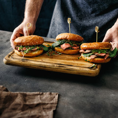 Male hands holding three burgers grilled beef meat dark background