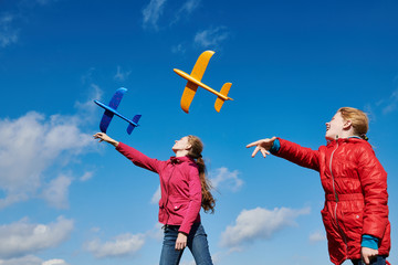 Girls playing with airplane at blue sky. Tand and childhood vacation concept