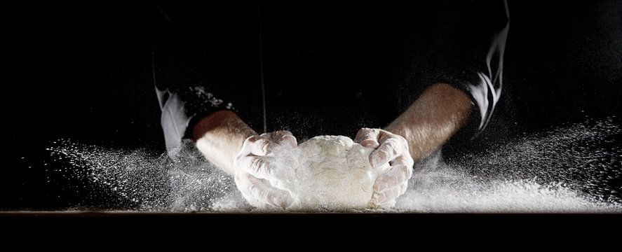 Cloud of flour caused by chef slamming dough