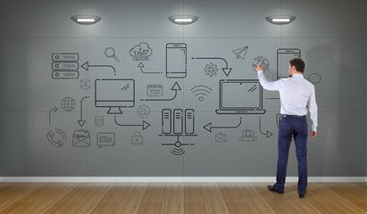 Businessman drawing tech devices and icons thin line interface on a wall