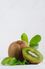Juicy ripe green kiwi with wet slice section, young leaf on white wood background, closeup, vertical. Healthy vegetarian food.