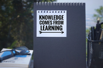 Educational and motivational  quote - 'Knowledge comes from learning' written on a white paper. Blurred styled background.