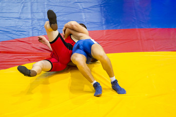 Two young men in blue and red wrestling on a yellow wrestling carpet in the gym