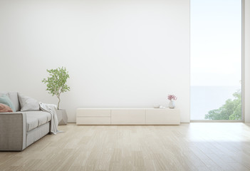 Wall Mural - Sea view living room of luxury summer beach house with TV stand and wooden cabinet. Empty white concrete wall background in vacation home or holiday villa. Hotel interior 3d illustration.