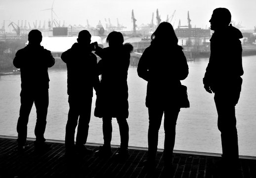 View of the port of Hamburg. Silhouettes of tourists