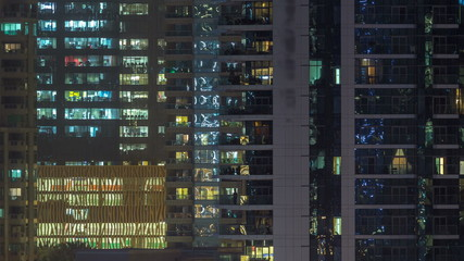 Glowing windows of skyscrapers at evening timelapse