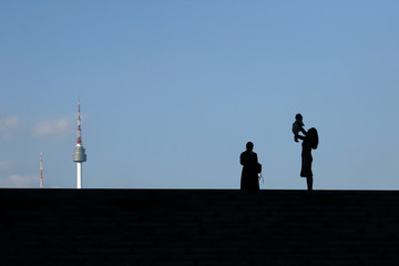 A woman holding up her baby is silhouetted against the backdrop of N Seoul Tower in Seoul