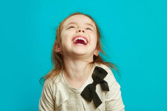 Joyful little girl laughs on blue background.