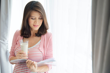Beautiful young Asian pink dress pregnant woman holding glass of calcium milk and reading a book standing in front of window with curtain. Modern healthy mom concept.