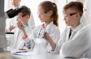 education, science and children concept - teacher and students with test tubes studying chemistry...
