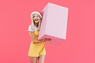cheerful young woman in christmas hat listening big gift box isolated on pink
