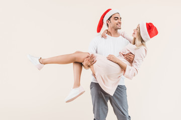 happy young man in santa hat carrying beautiful smiling girl isolated on beige