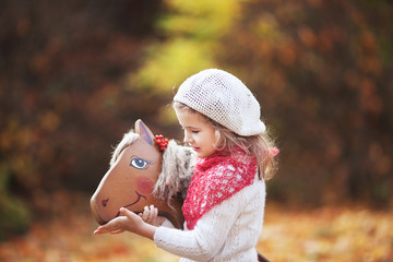 Cute little girl feeds a wooden toy horse in the autumn garden.