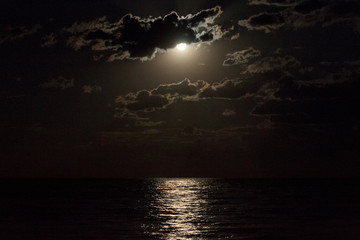 Full moon in a cloudy night sky reflecting moonlight on sea