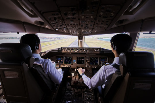 Two airliner pilots are flying the airplane towards the runway. Outside cockpit can see landing runway and environment with sun. Inside cockpit can see pilots and all flight instrument and equipment.