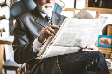 Close up image senior businessman hand with newspapers.
