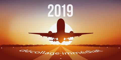 Carte de vœux 2019 avec un avion au décollage sur une piste d'aéroport, devant un coucher de soleil