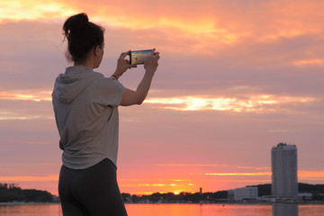 Caucasian woman in sport clothes taking photo on smartphone of sunset
