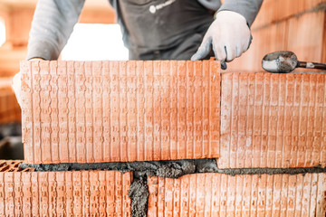 Bricklayer male construction worker installing interior brick masonry