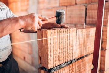 Bricklayer male worker installing interior walls with rubber hammer, level and putty knife