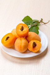 Bunch of apricots and half on a white plate