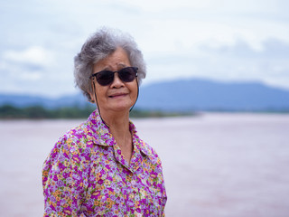 Portrait of elderly asian woman wearing sunglasses standing side the river.