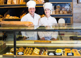 staff offering fresh baguettes and buns in bakery