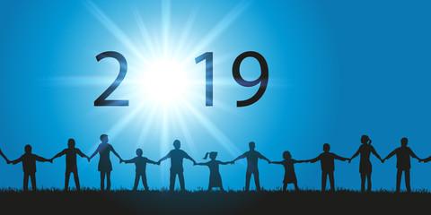 Carte de vœux 2019 montrant un groupe de personnes composé d'hommes et de femmes de tout âges, ainsi que des enfants se donnant la main face au soleil.