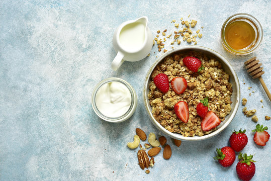 Multicereal homemade organic granola served with fresh strawberry, nuts, honey, milk and yogurt.Top view with copy space.