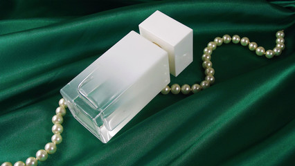 Perfume in a white bottle and beads of pearls on a green drapery.