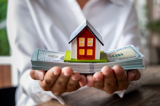 House model and money in hand, Concept of real estate and deal