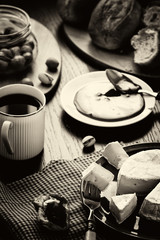 Breakfast in French, in European. Camembert cheese, jam, coffee, olives, fresh pastries and pistachio nuts