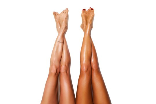 two beautiful pairs of smooth woman's legs after laser hair removal on the white background