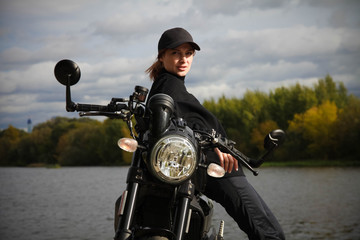 Woman and retro cafe racer motorcycle
