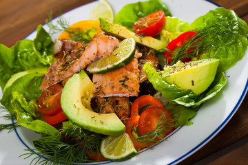Deliciously salad of  fried  trout with  avocado, greens and tomatoes