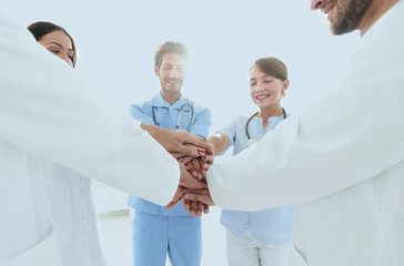 Doctors and nurses in a medical team stacking hands