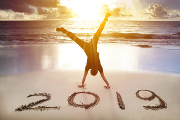 young man handstand on the beach.happy new year 2019 concept