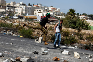 Palestinian demonstrator jumps as he hurls stones at Israeli troops during clashes at a protest near the Jewish settlement of Beit El, near Ramallah, in the occupied West Bank
